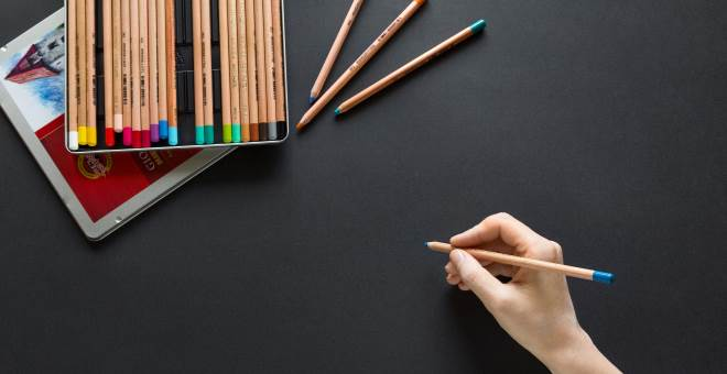 A hand holding one colored pencil from a nearby set